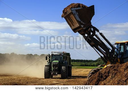 fertilize the field excavator with a shovel full of manure ready to fill the trailer of the tractor blue sky copy space selective focus