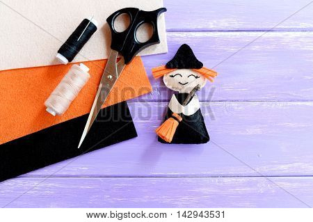 Funny Halloween witch made of felt, scissors, thread set, orange, beige and black felt sheets on wooden background with blank space for text. Halloween sewing crafts for kids. Inspiration DIY