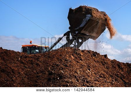 Excavator shovel working on a large heap of manure organic fertilizer for the field blue sky copy space