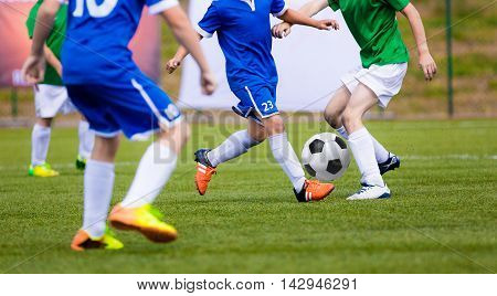 Soccer football game for kids. Young boys kicking soccer ball on the grass pitch