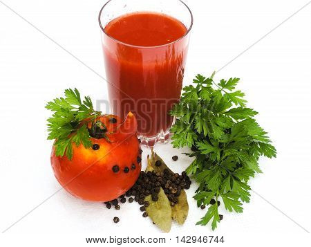 . Fresh tomato juice in a glass, funny tomato, spices and parsley leaves on a white background