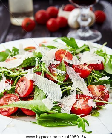 Close-up shot of summer, green salad made of fresh arugula leaves, halves of cherry tomatoes, grated parmesan and lemon zest on white plate. Dietary vegetarian simple dish on dark wooden background