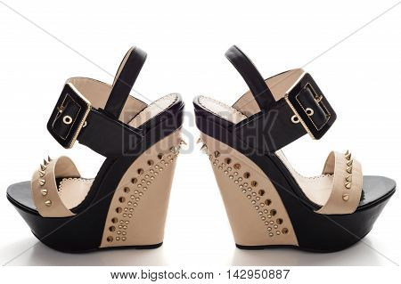 Female black platform shoes with beige inserts and studs isolated on white