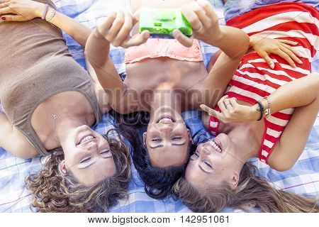 Group Of Pretty Girl Take A Selfie Lying In The Park