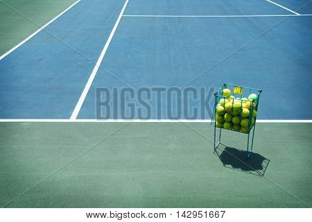 Tennis court with tennis balls in tennis ball basket stand by the baseline. Intentionally shot in surreal tone.