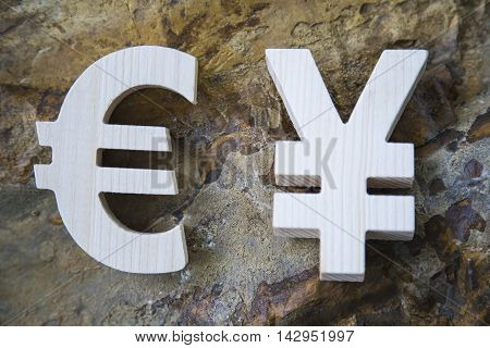 Exchange currency unit on a rock background. Wooden sign.