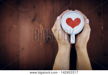 Man Holding Hot Cup Of Milk On Wood Table, With Red Heart Shape