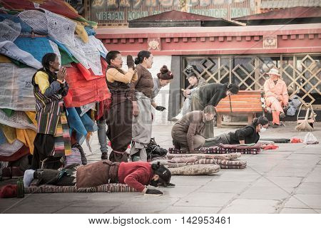 LHASA, TIBET - MAY 2016 - Tibetans perform prostration in front of Jokhang temple as a part of pilgrimage in Lhasa, Tibet, where they celebrate Sagadawa festival in May.