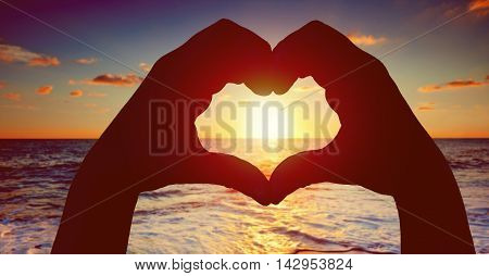 Silhouette Hands In Heart Shape With Sunset In The Middle And Beach Background