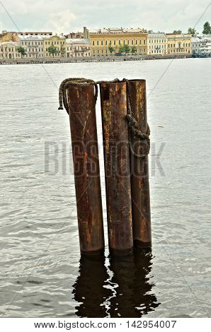 Iron pipe in the water.They stand at the shore for ships.