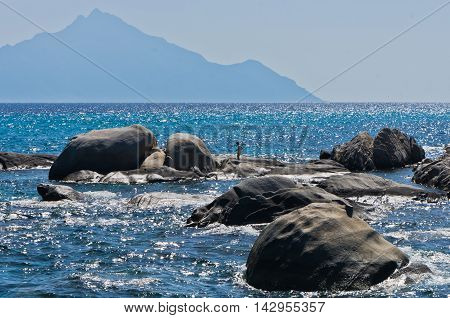 Sea rocks at greek coast with holy mountain Athos in background, Greece