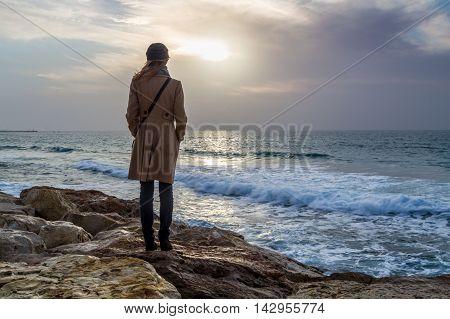The girl looks at the winter sea standing on a rock. Mediterranean sea in Tel Aviv, Israel