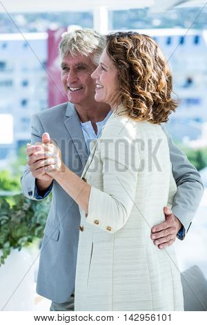 Smiling mature man holding woman hand