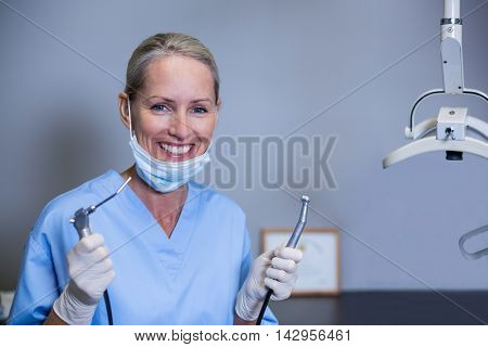 Portrait of smiling dental assistant holding dental tools in clinic