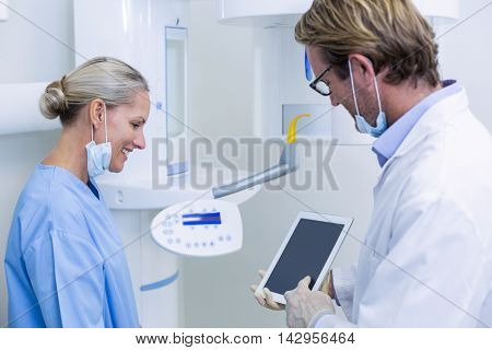 Dentist and dental assistant working on digital tablet in dental clinic