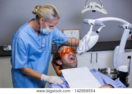 Dental assistant examining young patient mouth in clinic