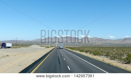 Interstate 40 in Arizona, United States of America; long, straight highway through the Mojave Desert in Arizona, two-lane roadway with marking and emergency lane, mountainous landscape and blue sky