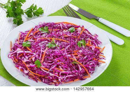 Salad coleslaw - red cabbage with carrots and parsley on white dish with fork and knife on green table mat authentic classic recipe view from above close-up