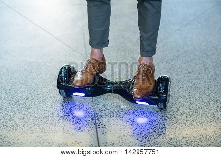 Graphic designer standing on hoverboard in office
