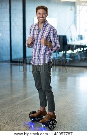 Portrait of graphic designer standing on hoverboard in office