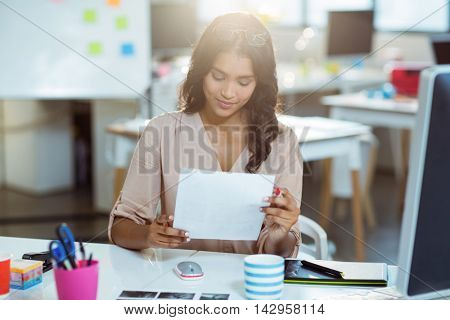 Graphic designer looking at color swatch in office