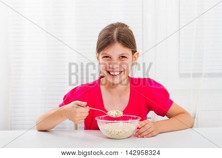 Cute little girl is sitting and eating cereals for breakfast.