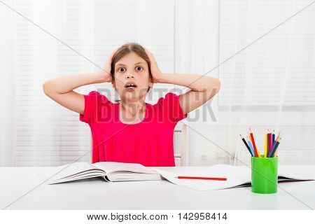 Little girl is in panic because of her homework.