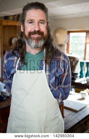 Portrait of male potter standing in pottery workshop in pottery workshop