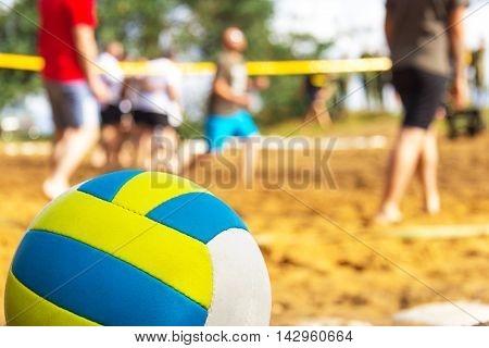 volleyball lies on playing field, people plays in background