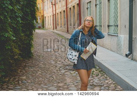 Young female tourist with map get lost on narrow street of scenic european old town