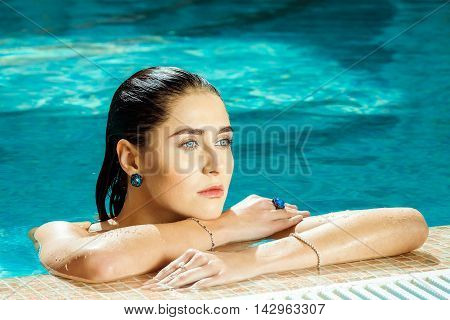 Woman in sad sapphires, on the edge of the pool side. Girl brunette with blue eyes swimming