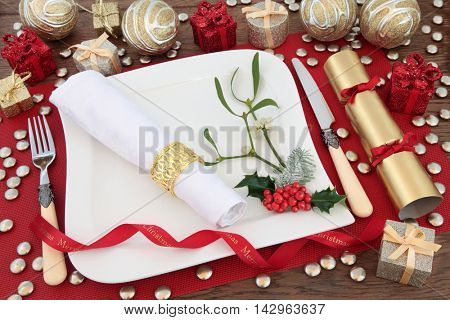 Christmas dinner table setting with white porcelain plate, linen napkin, antique cutlery, holly, mistletoe, bauble decorations, and cracker on red place mat over oak background.