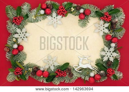 Christmas background border with silver snowflake, reindeer and bauble decorations, holly, mistletoe, snow covered spruce fir and pine cones on old parchment paper over red.