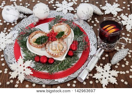 Christmas mince pie cakes with mulled wine, holly, winter greenery, white snowflake and luxury bauble decorations on oak background.