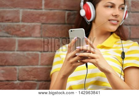 Girl listening to music with headphones and smart-phone