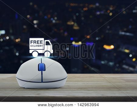 Wireless computer mouse with free delivery truck icon on wooden table over blur light city tower Transportation business concept