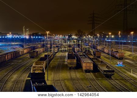 DUISBURG, GERMANY - MARCH 21, 2016: freight wagons lined up at night for loading at the freight yard of the steelplant HKM, one of the few sttelplants in Germany, still under operation
