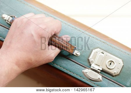 human hand holds the handle of the suitcase retro top view / travel with a suitcase in hand