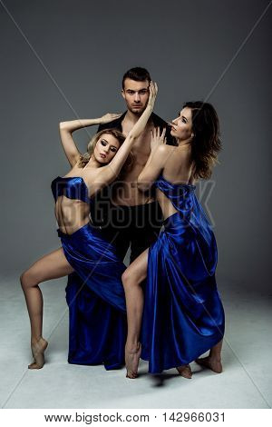 Beautiful young two women dancer in blue top, long blue skirt dancing with man