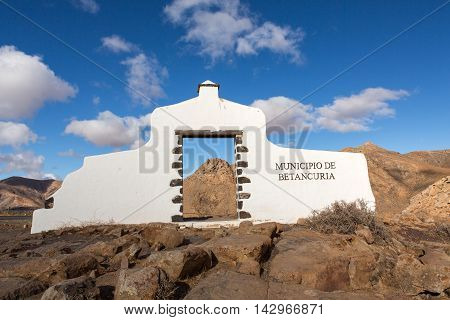 Typical municipality sign (white arch gate) near Betancuria village with desert mountain landscape in the background Fuerteventura Canary Islands Spain