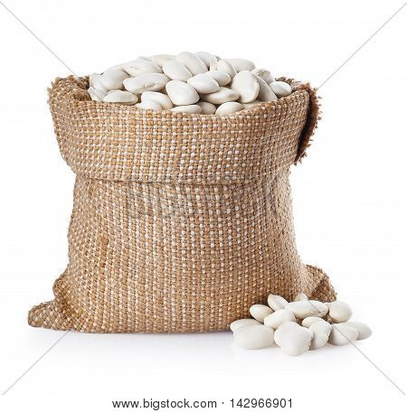 Butter beans or lima beans in a burlap bag with heap near bag isolated on white background. Dry white beans in burlap sack. Beans
