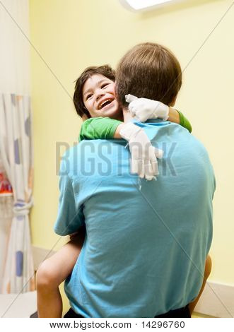 Little Boy Sitting In Doctor's Office, Laughing