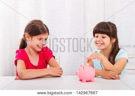 Cute little girls putting coin into piggy bank.