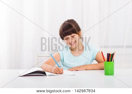 Cute little girl enjoys drawing and writing at her home.