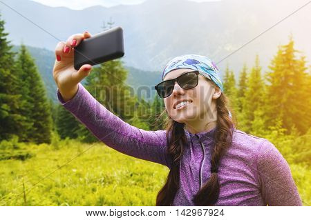 girl in the mountains makes selfie. Hiker makes a selfie uses the phone. Traveler make selfie on mobile phone at mountain outdoor. Selfie. Woman smiling and selfie on camera of mobile phone