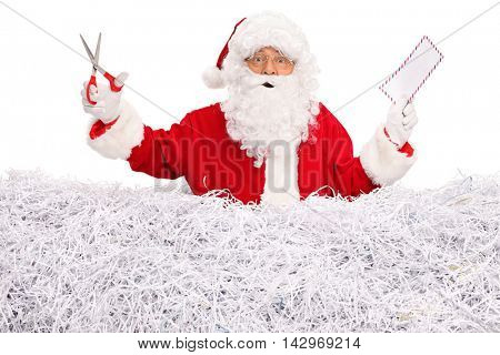 Santa Claus standing in a pile of shredded paper holding an envelope and a pair of scissors  isolated on white background