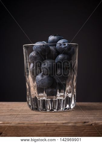 Blueberries in a glass on a wooden table super food concept image