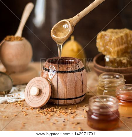 Honey background. Natural honey comb glass jarand wooden bowls. On wooden rustic table. Soft focus