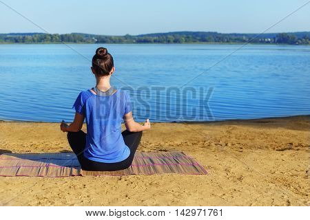 Yoga woman sitting on the river bank and meditating. Yoga girl in lotus pose back view. Young woman practicing yoga on mat outdoors at river bank. Healthy lifestyle. Yoga