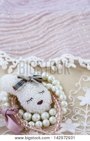 White brooch like head of hare with pink and white bracelets on pink lace as background